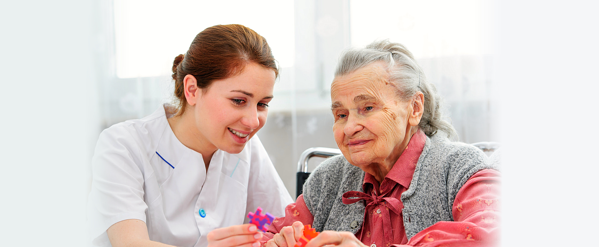 caregiver and elderly woman playing puzzle