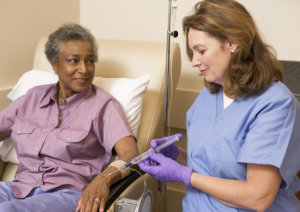 caregiver conducting IV therapy to her patient